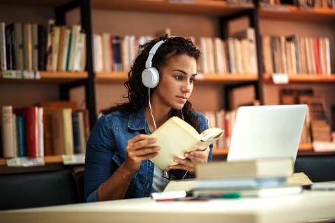Meisje met koptelefoon op studeert in bib